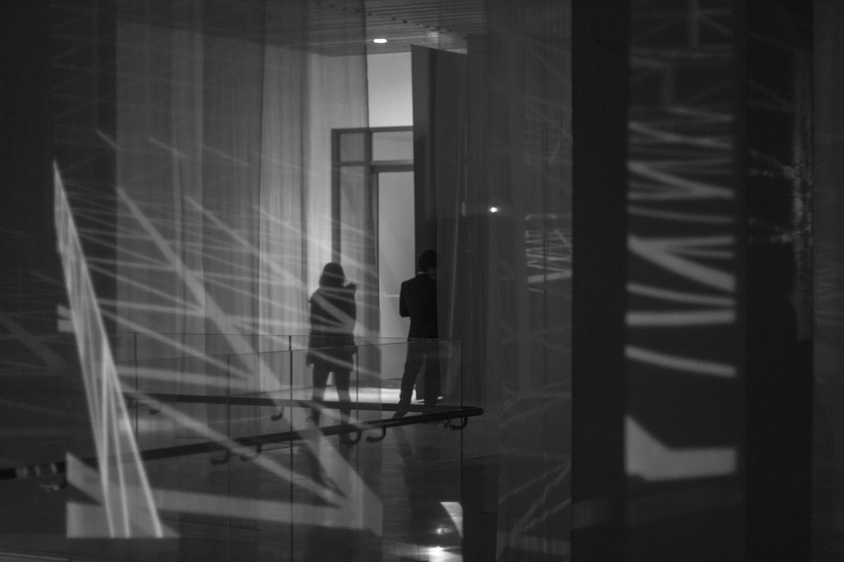 Silhouette of young woman, projection in space, lines, 3d, light and shadow, architecture, museum, photography